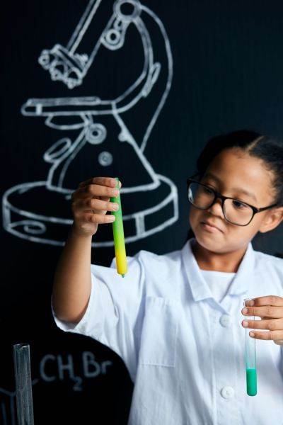 Asian American female child scientist holding tube during a experiment in lab