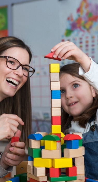 Mother and Daughter Playing Together with colorful building toy blocks