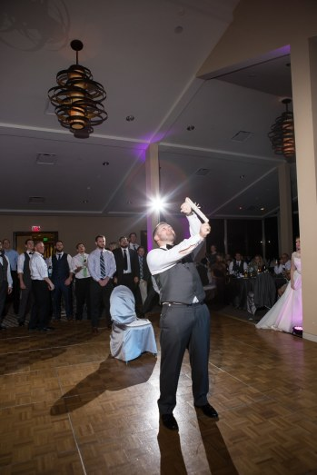 The groom readies the garter to be tossed to the waiting single guests.