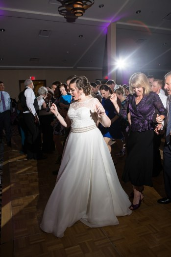 The bride enjoying a line dance at her wedding reception alongside her family and friends.