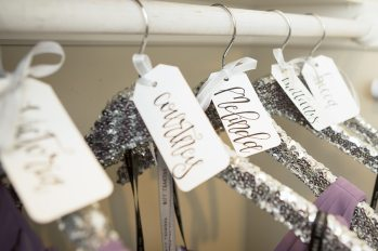 Custom hangers and hand-lettered name tags hold the bridesmaid's dresses.