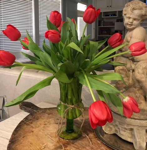 Bright red tulips in a green vase setting next to a stone cherub.