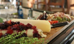 Stone fruit chutney over brie on a grazing board.