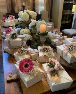 Table filled with flowers and boxed lunches.