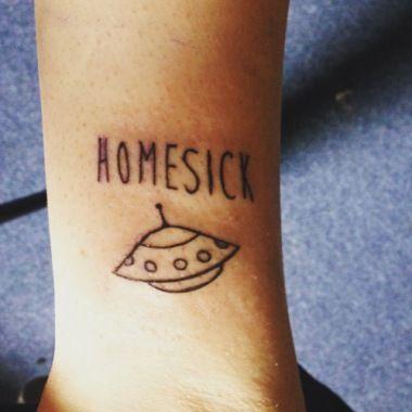 Spaceship tattoo with homesick scrip