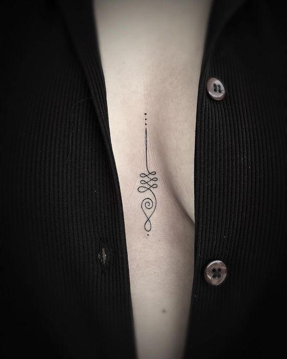 Minimalist unalome tattoo between breasts