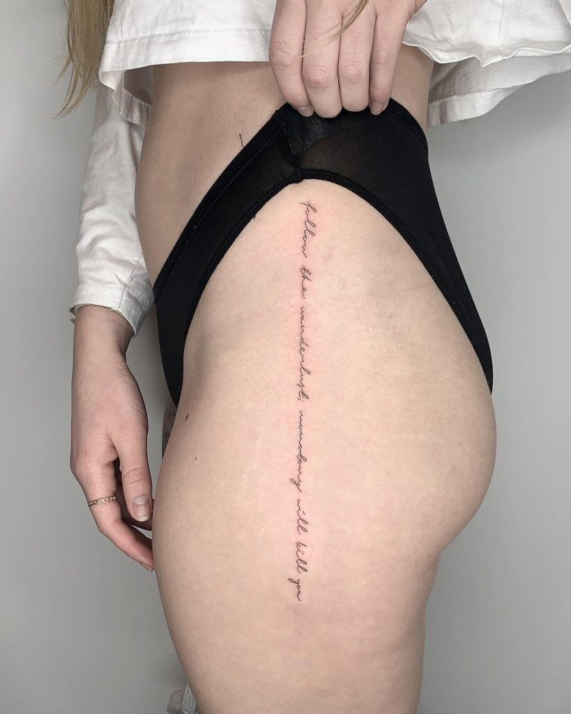 With style script vertical tattoo on hip