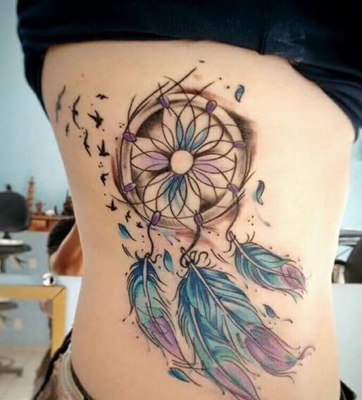 Dream catcher and birds tattoo on women ribs