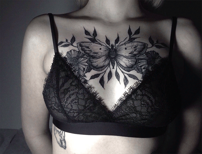 Moth tattoo with flowers on chest