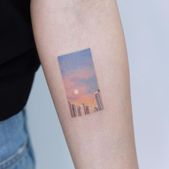 Sun set on city tattoo in frame