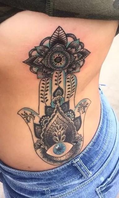 Hamsa symbol tattoo with blue detail