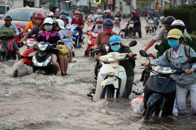 Cảnh tượng đường biến thành sông, người và phương tiện bì bõm trong biển nước mỗi khi mưa xuống đã trở nên phổ biến tại các đô thị, nhất là Hà Nội và Thành phố Hồ Chí Minh. (Nguồn ảnh: TTXVN)