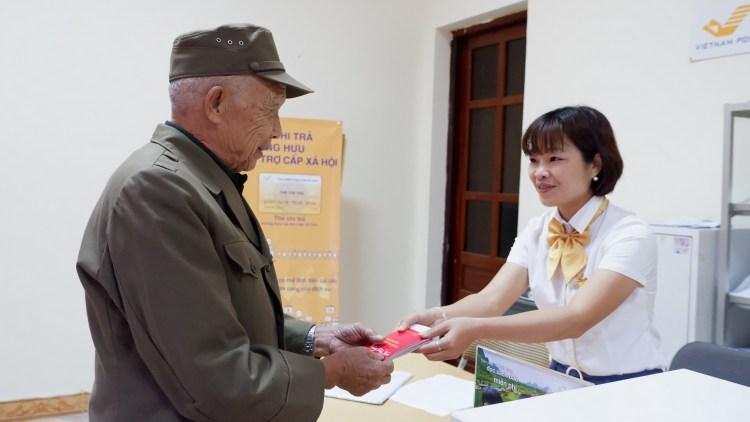 Cán bộ bưu điện chi trả lương hưu,trợ cấp xã hội. (Ảnh: PV/Vietnam+)