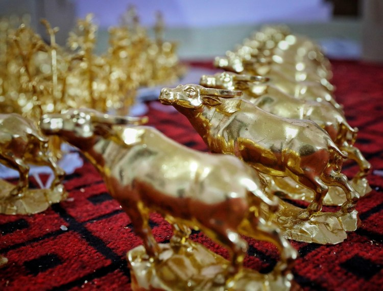 Gia đình nghệ nhân Nguyễn Anh Chung thếp vàng lên tượng trâu vàng cho khách hàng. (Ảnh: Danh Lam/TTXVN)