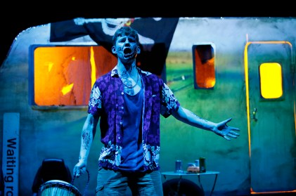 A bloodied actor standing in front of the projection-mapped caravan in the final scene of the play.