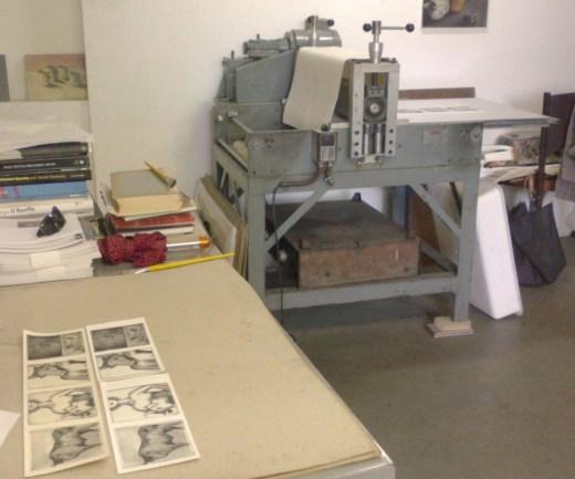 a prensa ao fundo com as gravuras impressas secando.