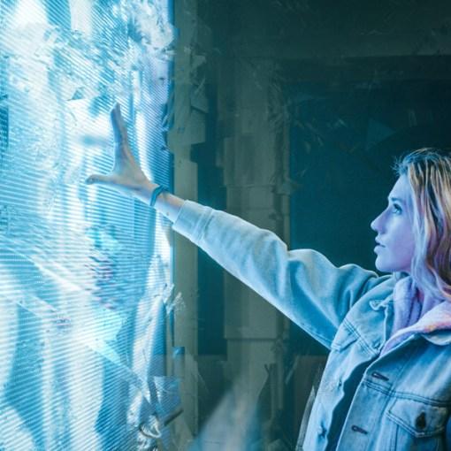 Une femme touche une image lumineuse sur le mur, peut-être un écran en relief.