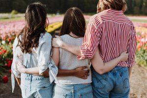 Tre flickor som håller varandra omryggen