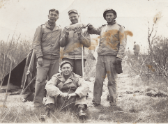 Dad  in front, with Army buddies. I think they're holding a fish.