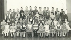 Me in front row, just right of center, in the dress with rows of black ribbon across bottom.