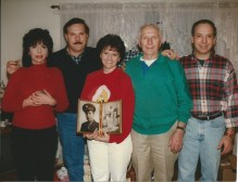 A family photo after mom passed, with me holding up her wedding photo, so she could be in the shot.