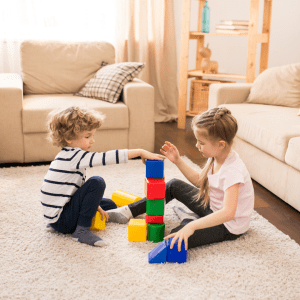 Young boy and young girl playing with blocks on the floor