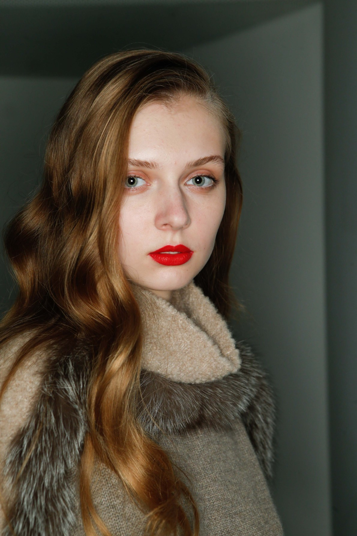 front view of a woman with red lipstick and honey blonde hair, sun kissed brown waves