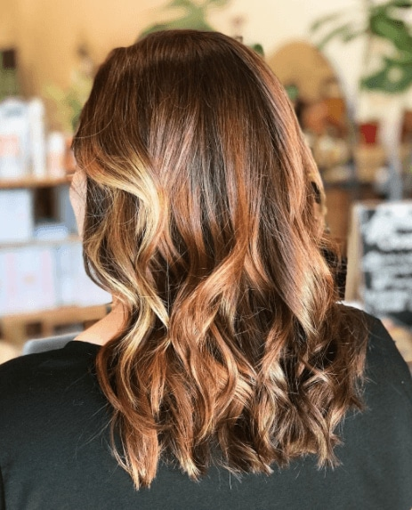 side view image of a woman with wavy hair with balayage in honey blonde hair colours