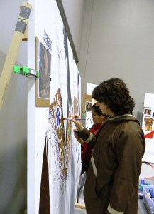 Sarah Obed and Dewey Kkotheyo Hoffman paint the Athabascan display. Photo by Angela Gonzalez