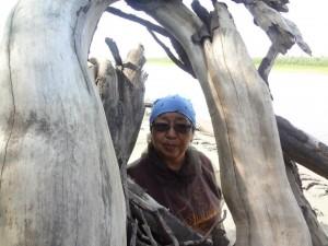 Eleanor Yatlin behind drift wood. Photo by Al Yatlin Sr.