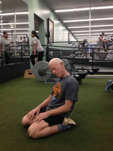 FitOldDog using his head during stretching in the weight room.