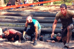 obstacle course race, runner running on mud