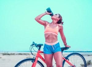 women drinking water while running