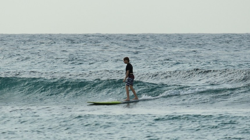 desmond standing up on surfboard at one of the western puerto rico beaches