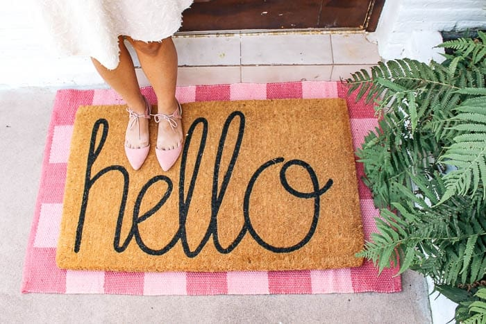 Front porch decor ideas for a small area. Create curb appeal with a simple trick, layer rugs under your doormat. Some fun picks to achieve the layered doormat look!