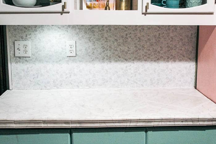 DIY peel and stick tile backsplash. Are you looking for a quick fix for your kitchen or bathroom back splashes? I share how to install vinyl marble hexagon removeable tile. It is super easy and needs no grout! Plus ideas for a variety of peel and stick tile that you can put on your backsplash!