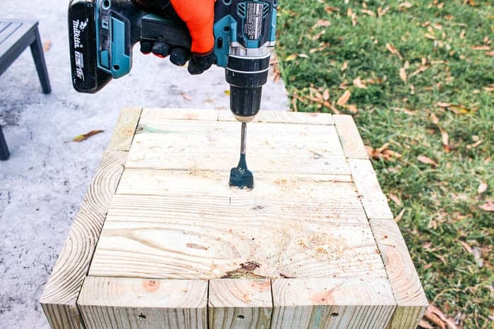 diy umbrella stand for an outdoor patio that works as a side table. How to make an umbrella base holder. This is an easy project made of wood with wheels and concrete. Plus it's cheap to make too! Click through for the tutorial and ideas for how to decorate your deck.