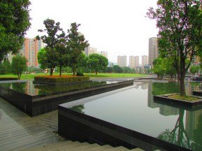 Trees sit on platforms in the middle of onyx pools that reflect tall buildings on top of them