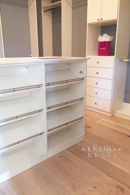 Master bedroom closet with a large shoe island and drawers for storage