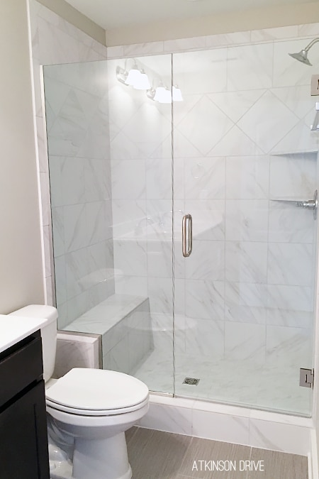 New Home: The master shower features a frameless glass door and marble-imitation ceramic tile