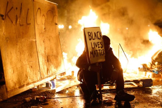 'Black-Lives-Matter'-protester-street-fire-Oakland-112414-by-Stephen-Lam-Reuters