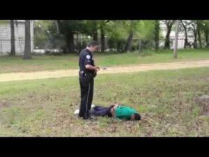 Slager stands over Scott's body, though in police report he claims he performed CPR