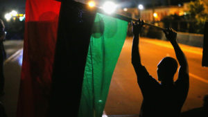 FERGUSON, MO - AUGUST 12:  Demonstrators hold up a Pan-African flag to protest the killing of teenager Michael Brown on August 12, 2014 in Ferguson, Missouri. Brown was shot and killed by a police officer on Saturday in the St. Louis suburb of Ferguson. Ferguson has experienced two days of violent protests since the killing but, tonight's protest was peaceful.  (Photo by Scott Olson/Getty Images)
