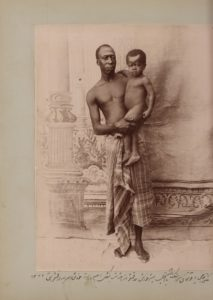 In this staged photo taken by Zell-e Soltan at his summer hunting palace near Isfahan, one of his African slaves holds his son. According to the caption, the infant (Iqbal) is the real son of the adult African slave, Haji Yaqut Khan, suggesting he wasn't a eunuch and could father his own children. The caption says that Yaqut Khan is in his ethnic clothes (languteh), which was mainly worn by Africans outside of Iran. Photograph: Zell-e-Soltan/Modern Conflict Archive, London, UK