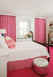Vivian's accent color of choice—red—takes a slightly softer tone in her daughter's bedroom, where large doses of bright pink are beautifully balanced with equal amounts of white.