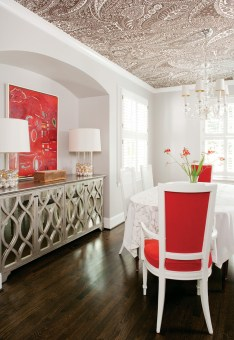 In the dining room—and throughout the house—a neutral palette prevails, interspersed with pops of red. Reclaimed oak flooring replaced ceramic tile in this space; stained to match the home's existing hardwood floors, it allows for a seamless transition from room to room.