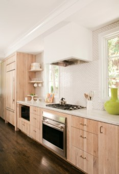 """In keeping with the Bencichs' quest to """"go green,"""" limed wax-finished cabinets in the kitchen were locally sourced. Open shelving keeps everything within arm's reach. Without visible hinges, cabinet doors and drawers create a seamless façade."""