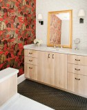 Although it features the same cabinetry as that in the kitchen and the same neutral scheme found throughout the house, the master bath has singular style thanks to a bold choice of wallpaper.