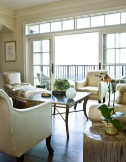 This end of the living room has a more informal air, thanks in part to the transom-topped French doors that open to a balcony. The pair of chairs is by Rose Tarlow and the berg�?¨re and ottoman are by Nancy Corzine, all available through Ainsworth-Noah.