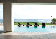 """In the living room, a sofa is strategically positioned to take full advantage of the breathtaking Gulf view while, opposite it, a backless version of the seating piece keeps the vista clear. Heron charcoal artwork from Sandler Hudson Gallery. The view from the living room is completely unobstructed, looking toward the zero-edge pool and the ocean beyond. Thanks to giant sliding glass doors that pocket into the walls, """"There's no visual boundary between the living room and the Gulf of Mexico,"""" Summerour notes."""